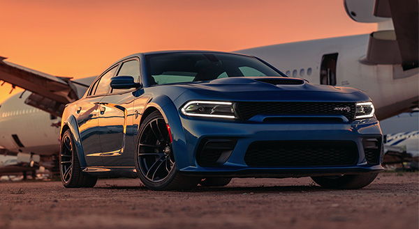 The blue 2020 Dodge Charger SRT<sup>®<\/sup> Hellcat parked in an airplane graveyard during sunset